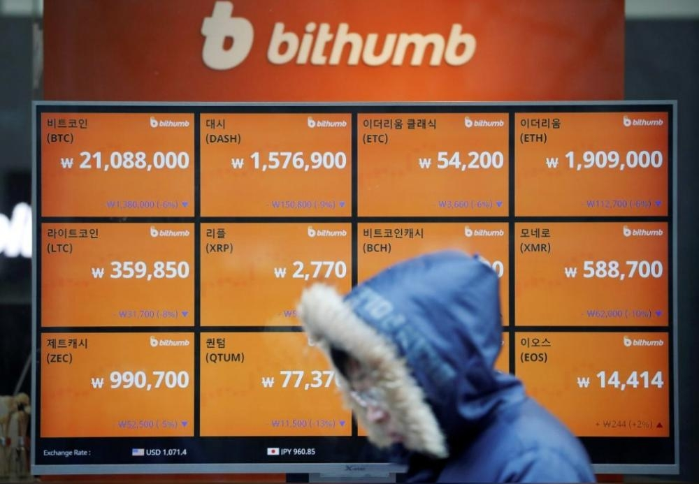 A man walks past an electric board showing exchange rates of various cryptocurrencies at Bithumb cryptocurrencies exchange in Seoul, South Korea, in this file photo. — Reuters