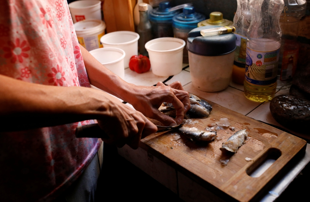Yaneidi Guzman, 38, prepares sardines in her kitchen at home in Caracas, Venezuela, in this Feb. 17, 2019 file photo. — Reuters