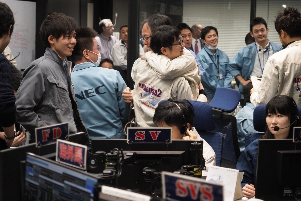 In this handout photograph taken and released by the Institute of Space and Astronautical Science (ISAS) of Japan Aerospace Exploration Agency (JAXA) on Friday, Yuichi Tsuda, center right, project engineer of the Hayabusa2 mission, hugs his colleague in the control room in Sagamihara, after the touchdown of the probe on the Ryugu asteroid. — AFP