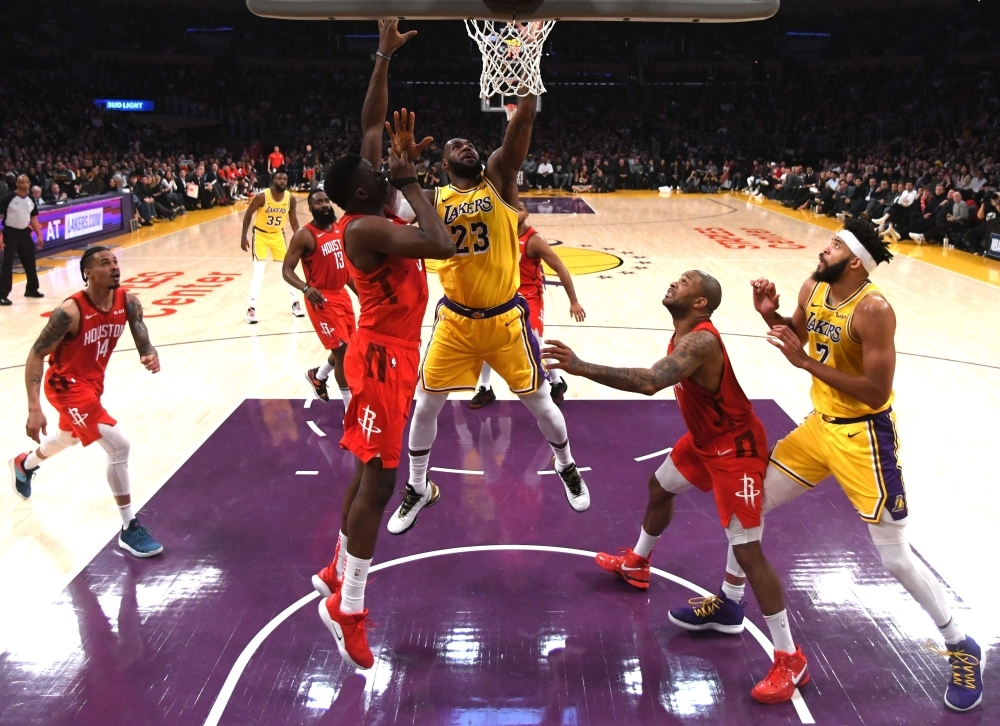 LeBron James No. 23 of the Los Angeles Lakers scores in front of Clint Capela No. 15 of the Houston Rockets as JaVale McGee No. 7 and PJ Tucker No. 17 look on during a 111-106 Lakers win at Staples Center on Thursday in Los Angeles, California. — AFP