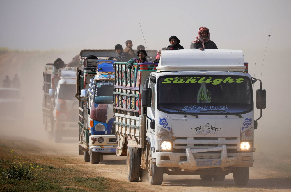 Trucks loaded with civilians ride near the village of Baghouz, Deir Al Zor province, Syria, on Friday. — Reuters