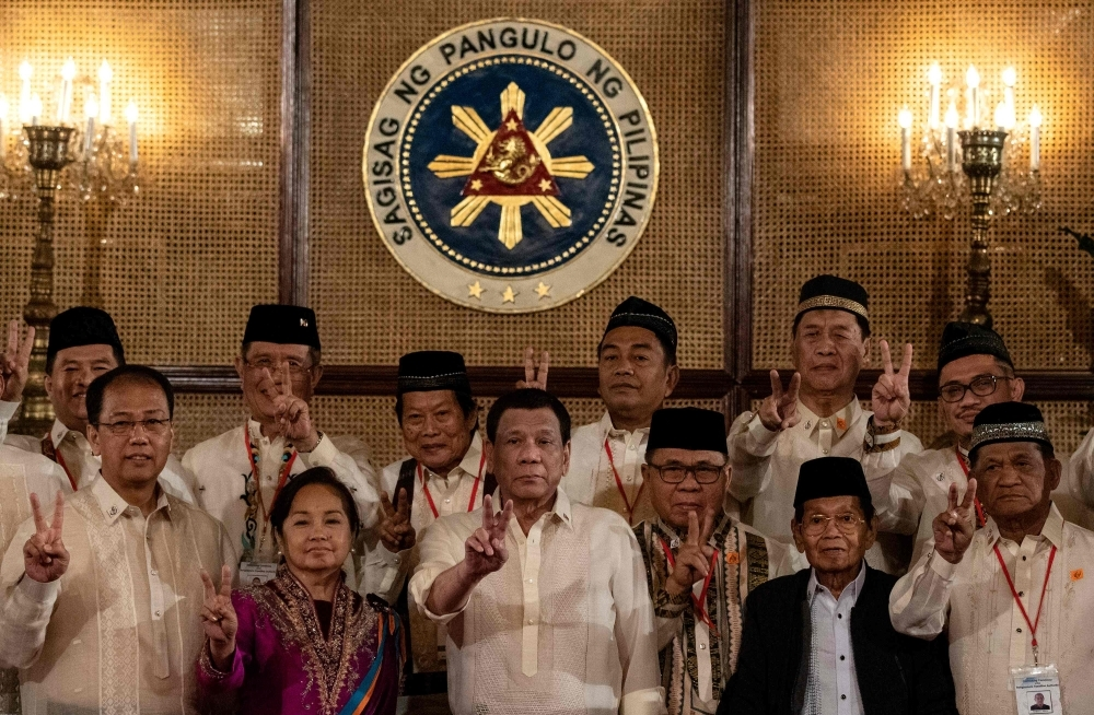 Philippine President Rodrigo Duterte, front center, gives a peace sign with Moro Islamic Liberation Front (MILF) chairman Murad Ebrahim, front third right, during the Ceremonial Confirmation of the Bangsamoro Organic Law Plebescite Law Canvass Results and Oath-taking of Transition Authority at the Malacanang palace in Manila on Friday. — AFP