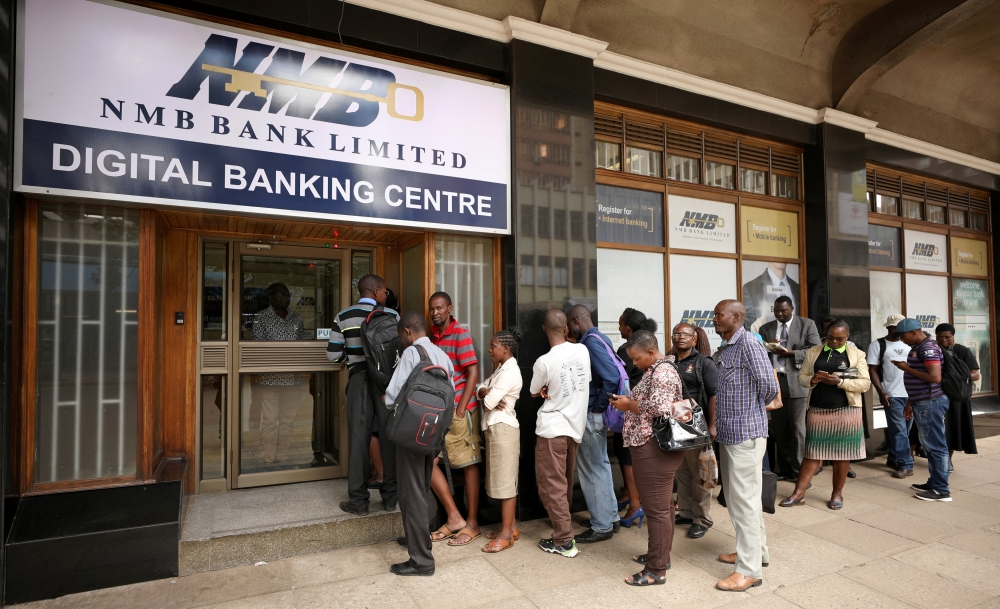 People queue outside a bank in Harare, Zimbabwe on Friday. — Reuters