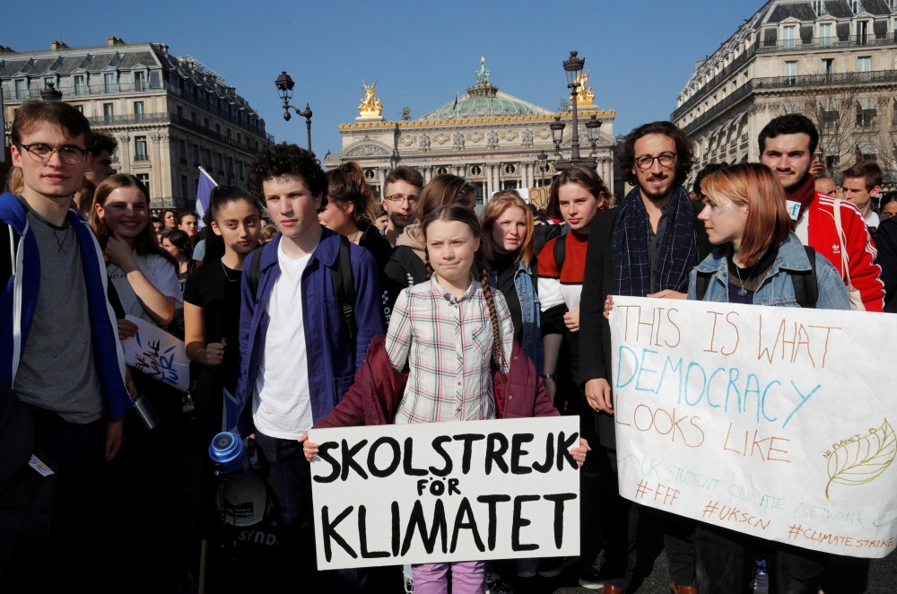 16-year-old Swedish environmental activist Greta Thunberg, holding a banner, and Anuna De Wever, a Belgian climate student activist, take part in a protest claiming for urgent measures to combat climate change, in Paris, France, on Friday. — Reuters