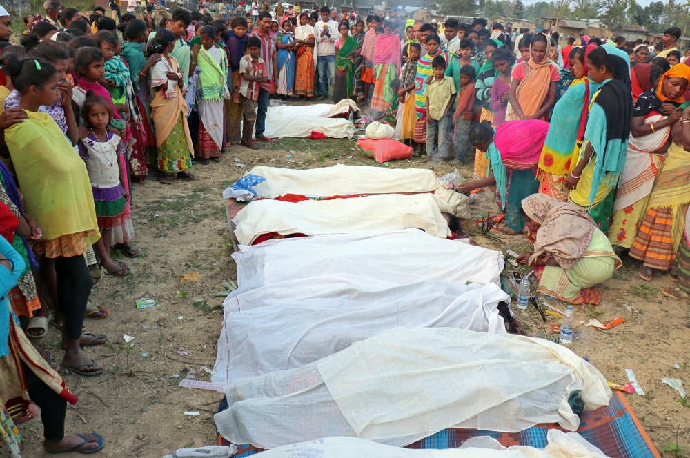 People stand next to the bodies of tea plantation workers, who died after consuming bootleg liquor, in Golaghat in the northeastern state of Assam, India, on Friday. — Reuters