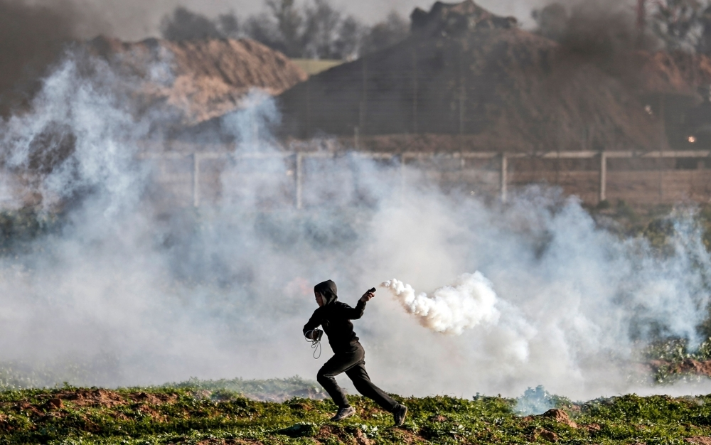 A Palestinian protester returns a tear gas canister thrown by Israeli troops during a demonstration near the fence along the border with Israel, east of Gaza City, on Friday. — AFP