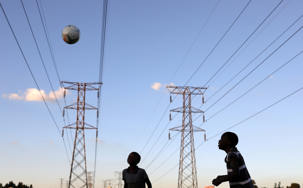 Boys play soccer below electricity pylons in Soweto, South Africa, in this Feb. 20, 2019 file photo. — Reuters