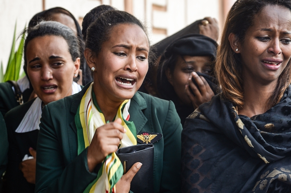 Mourners of victims of the crashed accident of Ethiopian Airlines react during the mass funeral at Holy Trinity Cathedral in Addis Ababa, Ethiopia, on Sunday. — AFP