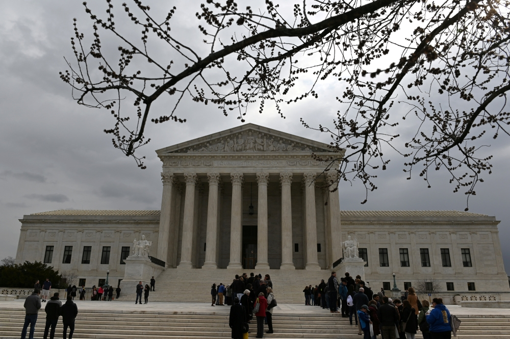 People wait in line outside the US Supreme Court to hear the orders being issued in Washington on Monday. — Reuters