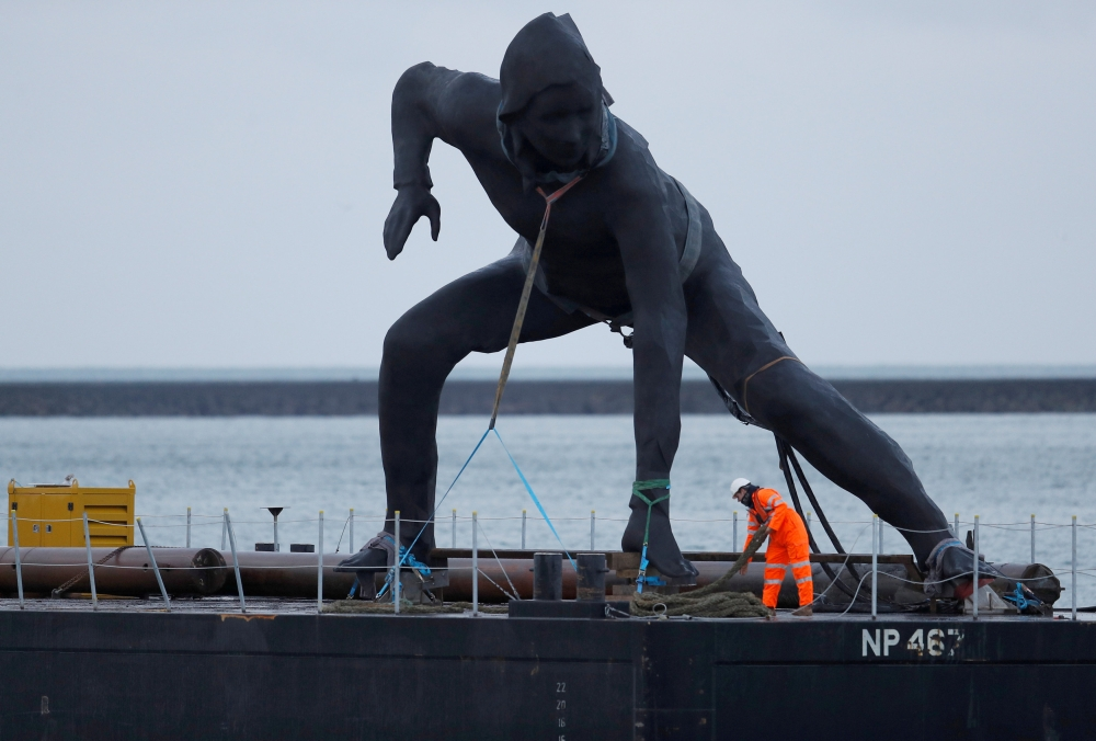 Britain's largest bronze sculpture arrives by barge in Plymouth Sound before being taken by road to the Theater Royal in Plymouth, Britain. — Reuters