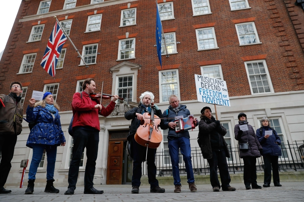 British-German musician Simon Wallfisch, center, poses playing the cello with supporters outside Europe House in Smith Square in London on Jan. 10, 2019 during a performance to protest Britain's exit from the European Union (Brexit). — AFP