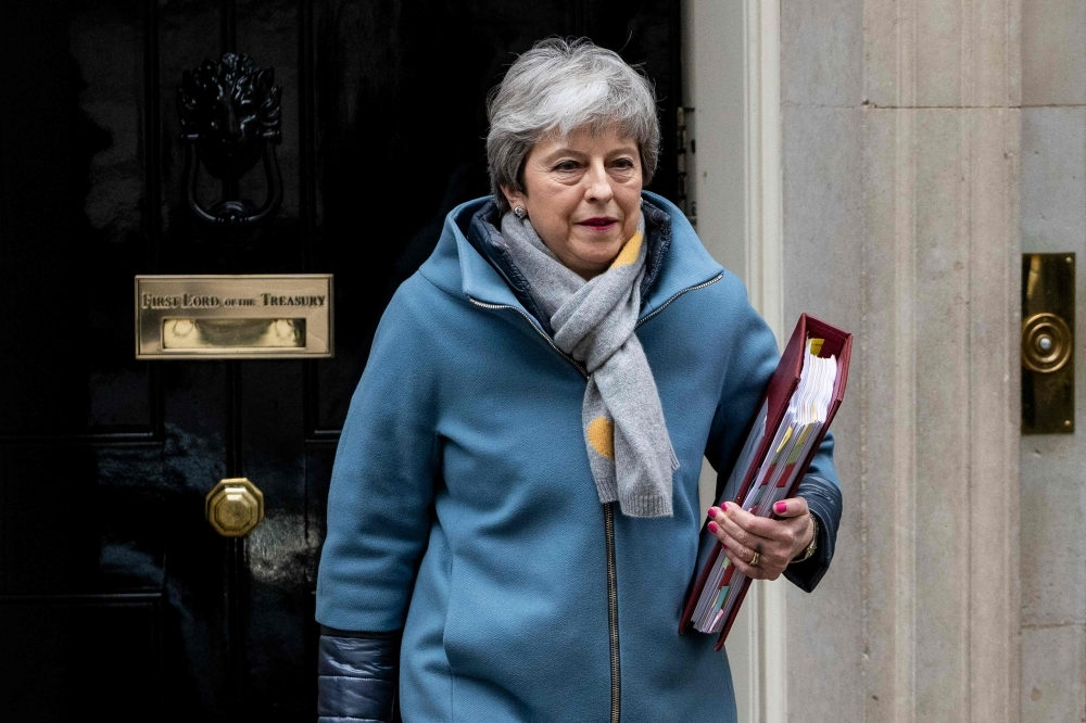 Britain's Prime Minister Theresa May leaves 10 Downing Street in London on Wednesday ahead of the weekly Prime Minister's Questions (PMQs) session in the House of Commons. — AFP