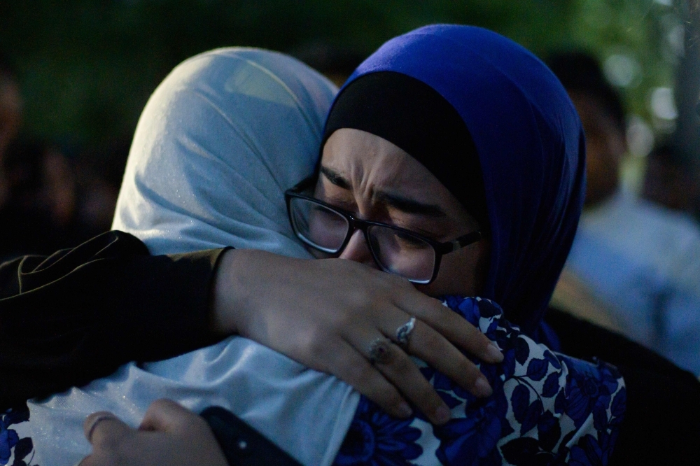 Two women cry and hug after watching a performance of the haka in front of the Al Noor mosque as a tribute to victims in Christchurch on Wednesday, five days after the twin mosque shootings claimed the lives of 50 people. — AFP