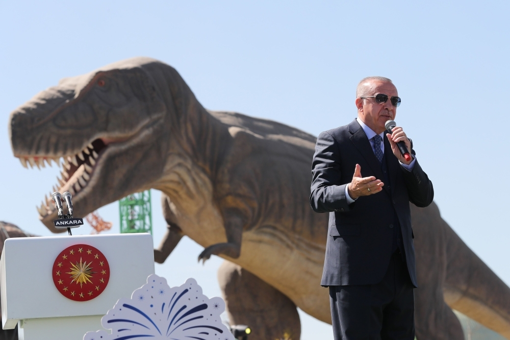 Turkish President Recep Tayyip Erdogan delivers a speech next to a model dinosaur during the opening ceremony of the Wonderland Eurasia theme park in Ankara. — AFP