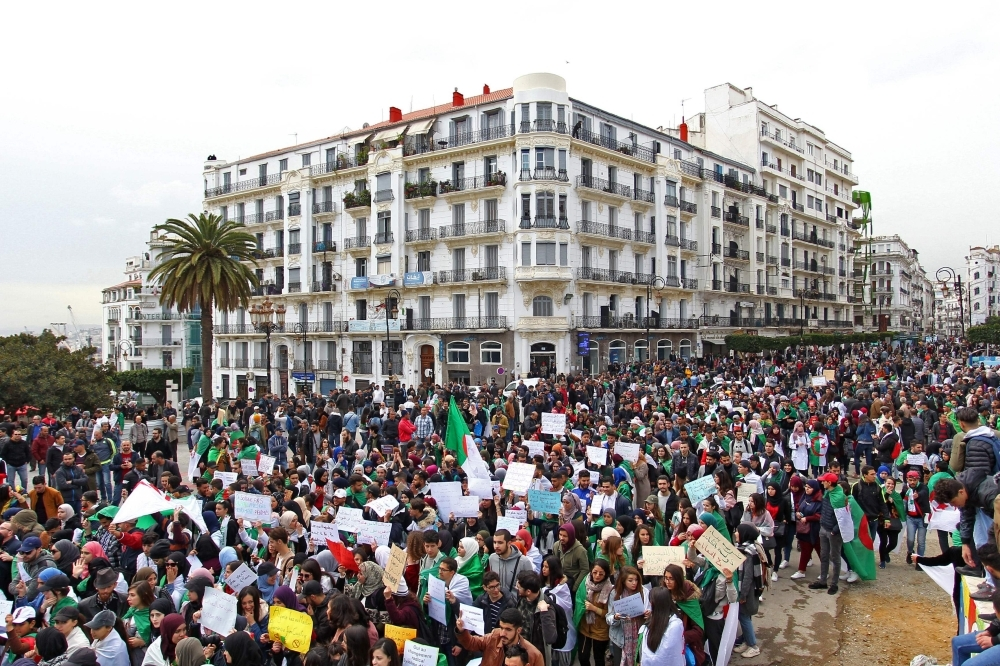Algerians carry placards and national flags as they take part in a demonstration in the capital Algiers against President Abdelaziz Bouteflika on Tuesday. — AFP