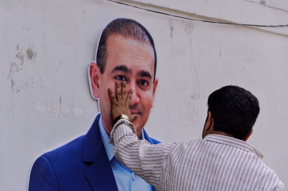 An Indian supporters of the Congress Party keeps his hand on the face of a cut out of billionaire jeweler Nirav Modi during a protest in New Delhi in this Feb. 16, 2018 file photo. — AFP