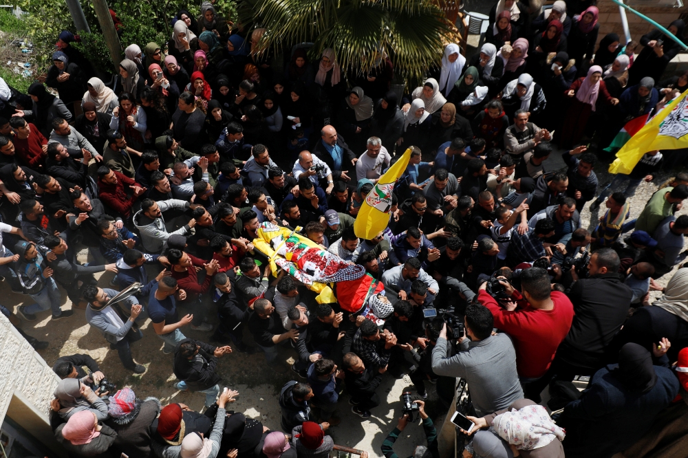 Mourners carry the body of Palestinian Ahmed Manasrah, during his funeral near Bethlehem, in the Israeli-occupied West Bank, on Thursday. — Reuters