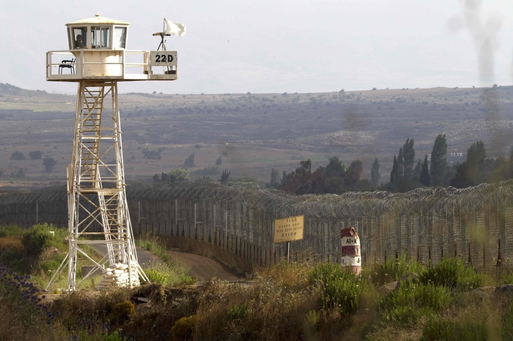 A file photo taken on the Israeli-occupied Golan Heights on July 18, 2013 shows a United Nations peacekeeper sitting in a watchtower near the Quneitra crossing in the demilitarized United Nations Disengagement Observer Force (UNDOF) zone. — AFP