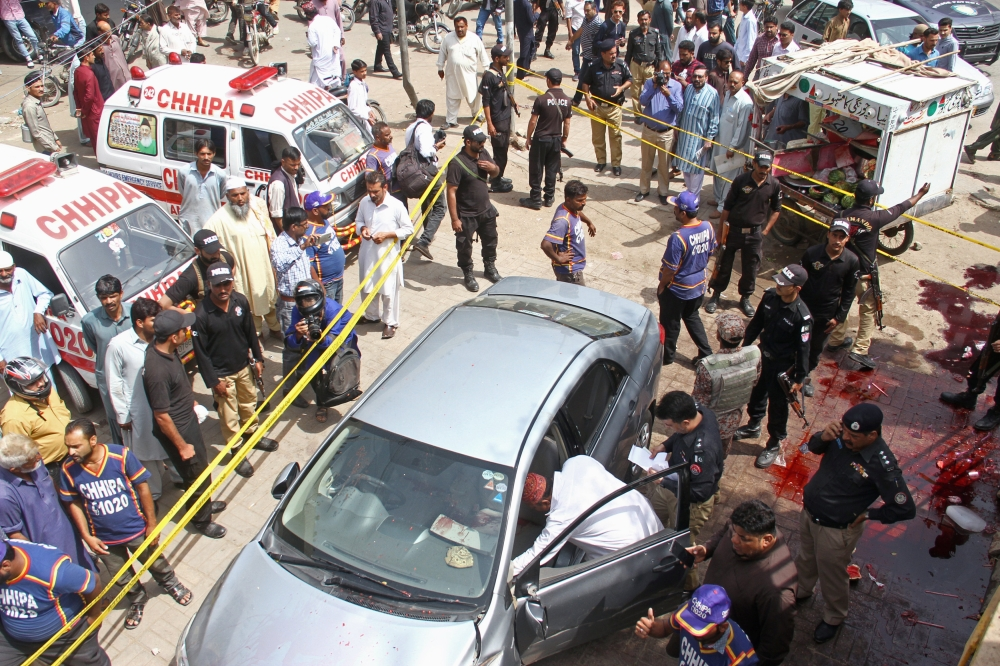 Police officers inspect a car after unidentified gunmen carried an attack on a prominent Pakistani cleric in Karachi, Pakistan, on Friday. — Reuters