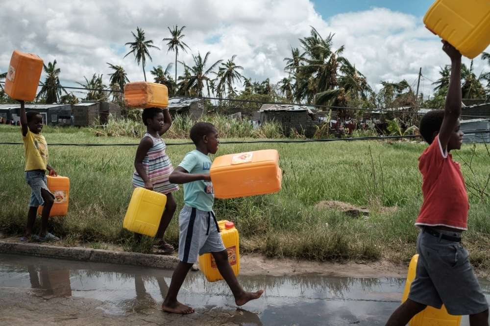 Children carry empty tanks to get water in Beira, Mozambique, on Thursday. — AFP