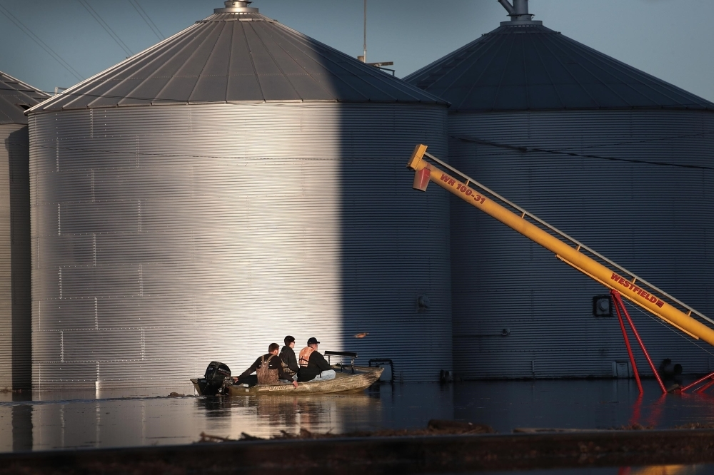 A boat passes by grain bins which are surrounded by floodwater in Craig, Missouri, on Thursday. — AFP