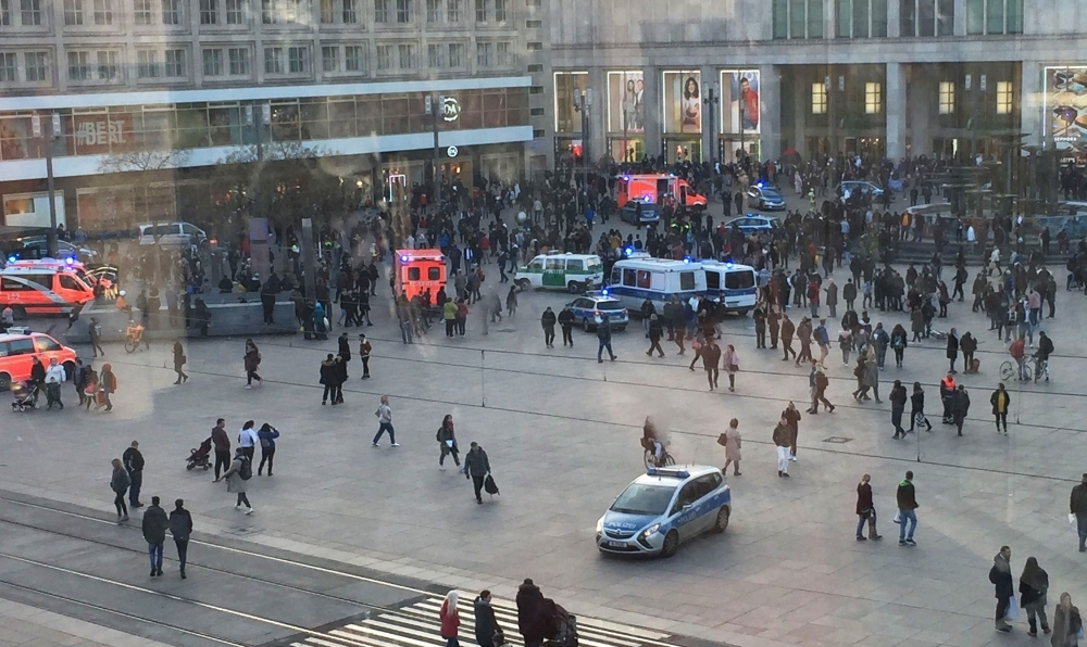Picture taken through a window shows people standing around police cars and ambulances at Alexanderplatz square in Berlin on Thursday. — AFP