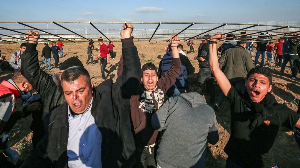Palestinians chant slogans as they march carrying a steel-wire mesh during a protest at the border fence with Israel east of Gaza City on Friday. — AFP