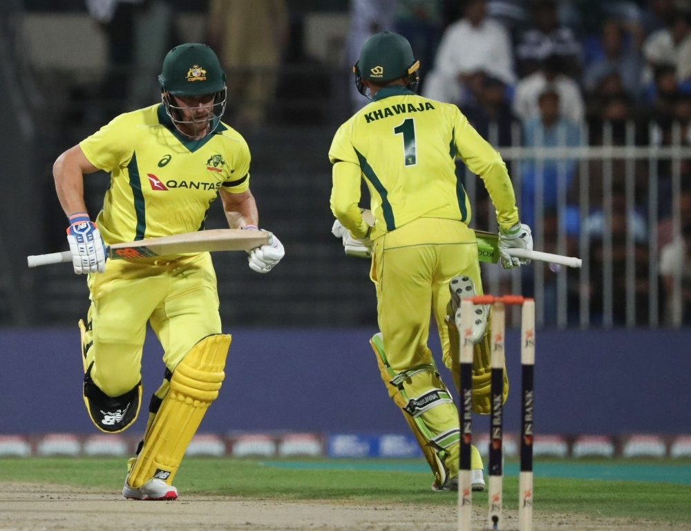 Usman Khawaja (R) and Aaron Finch of Australia run between the wickets during the first one-day international (ODI) cricket match between Pakistan and Australia at Sharjah Cricket Stadium in Sharjah on Friday. Australia won by eight wickets. — AFP