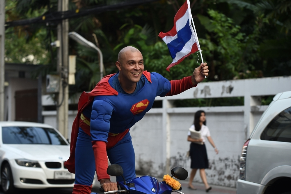 Thai-German national David Pfizenmaier performs a bike stunt whilst encouraging Thais to vote in the upcoming election in Bangkok. – AFP