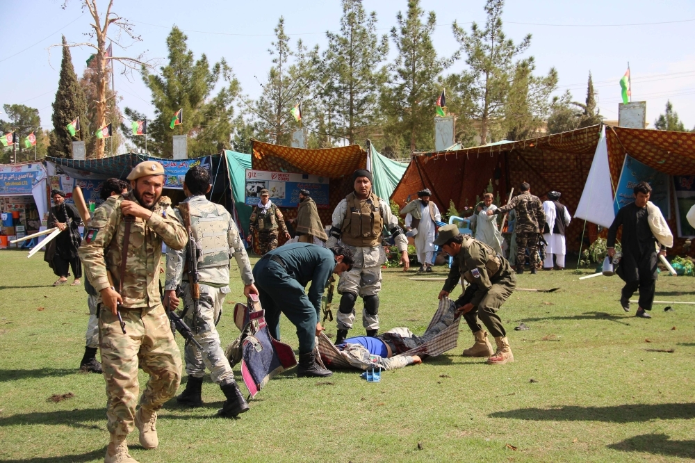 Afghan security personnel carry a victim following twin explosions in Lashkar Gah, the capital of Helmand province, Saturday. At least three people were killed and 30 wounded in twin explosions inside a stadium hosting an agricultural show in southern Afghanistan, officials said. — AFP