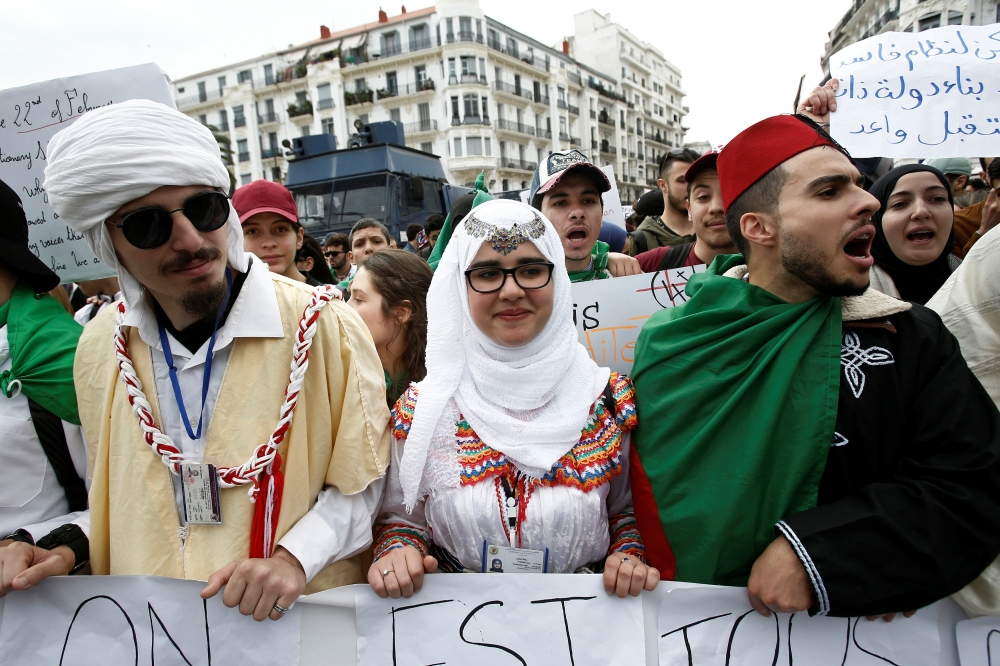 Students wearing traditional clothes hold banners and shout slogans during a protest calling on President Abdelaziz Bouteflika to quit, in Algiers, Algeria, Tuesday. — Reuters
