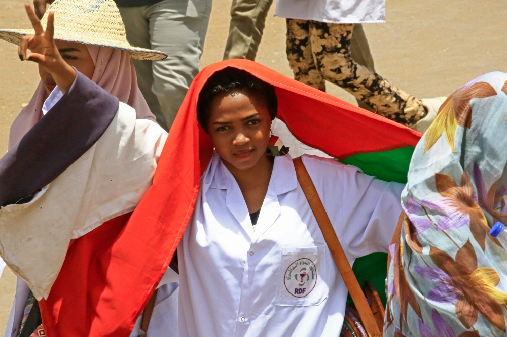Sudanese protesters wave signs as they continue to protest outside the army complex in the capital Khartoum on Wednesday. — AFP