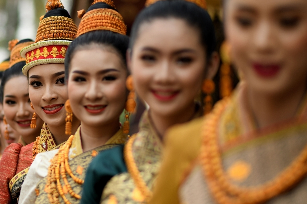 Miss Laos New Year or 'Nang Sang Khan' pageant winner Mila Douangximay (2nd L) along with the other chosen contestants, each symbolizing King Kabinlaphom's seven daughters, taking part in the annual Laos New Year or 'Pi Mai' celebrations at the Wat Xiengthong Buddhist temple in Luang Prabang.  — AFP