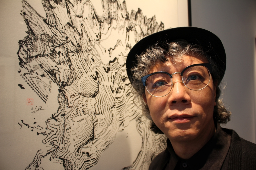 Hong Kong artist Victor Wong stands next to an artwork from his exhibition 'Far Side of the Moon' at 3812 Gallery in London. — Reuters