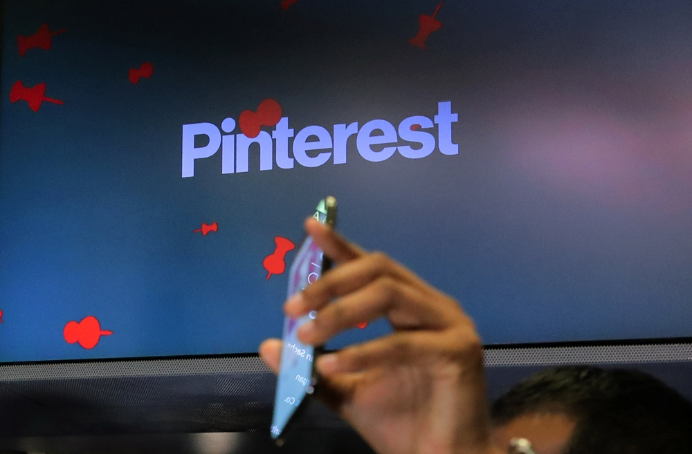 A guest hold up a phone during the Pinterest Inc. IPO on the floor of the New York Stock Exchange (NYSE) in New York, US, Thursday. — Reuters
