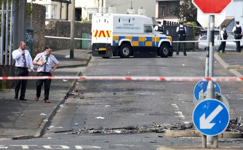 Police detectives inspect the scene where a journalist was fatally shot amid rioting overnight in the Creggan area of Derry (Londonderry) in Northern Ireland on Friday. — AFP
