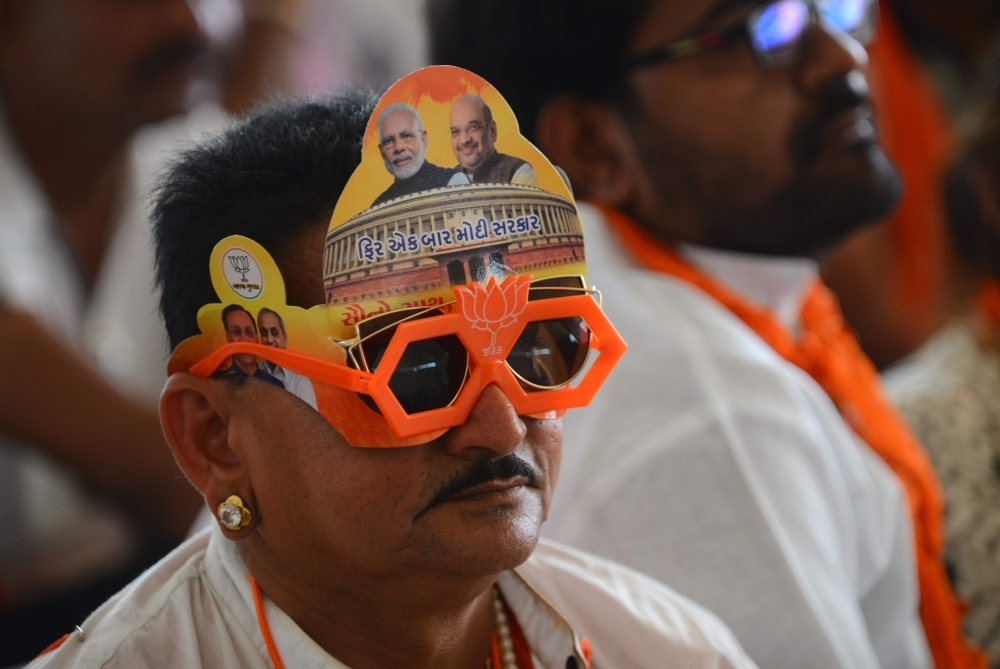 An Indian supporter of the Bhartiya Janta Party (BJP) wears the party's symbol and photos of Indian Prime Minister Narendra Modi and BJP President Amit Shah during a rally in Amreli, some 250 km from Ahmedabad, on Thursday. — AFP