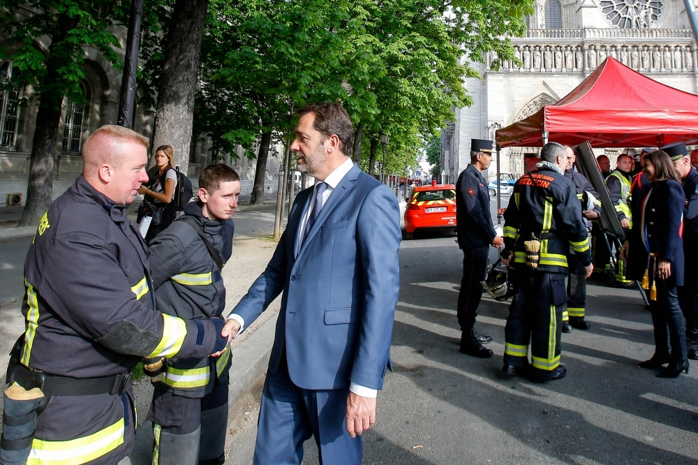 French Interior Minister Christophe Castaner, third left, shakes hands to a firefighter as he tours Notre Dame cathedral in Paris on Thursday. — AFP