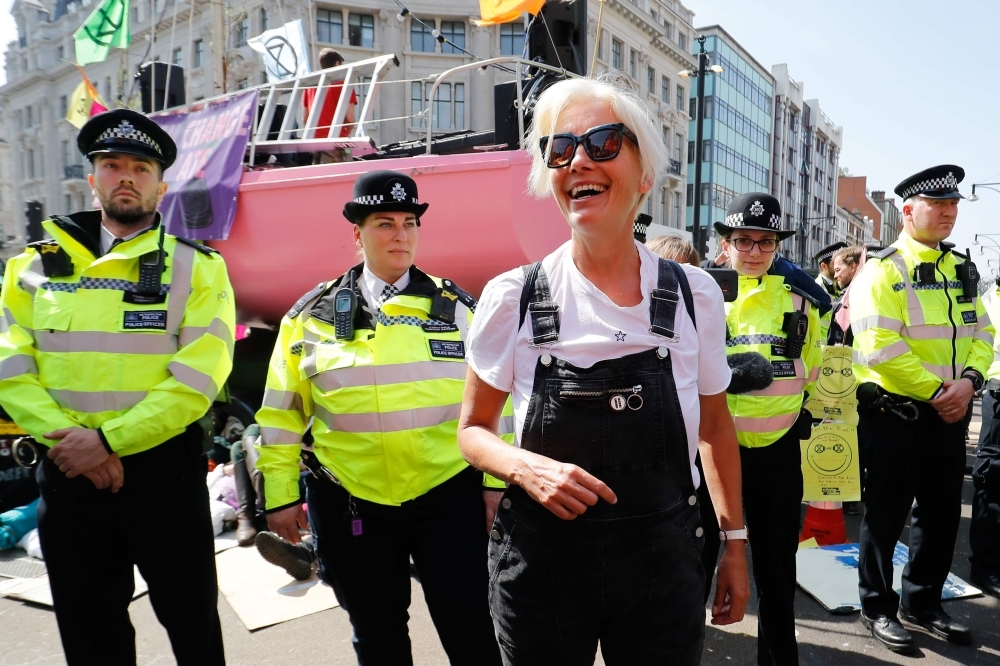 British actress Emma Thompson, center, gestures as police surround the pink boat being used as a stage by climate change activists as they occupy the road junction at Oxford Circus in central London on Friday during the fifth day of an environmental protest by the Extinction Rebellion group. — AFP