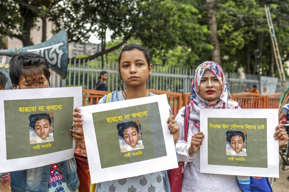 Bangladeshi women hold placards and photographs of schoolgirl Nusrat Jahan Rafi at a protest in Dhaka on April 12, 2019 following her murder by being set on fire after she had reported a sexual assault. — AFP