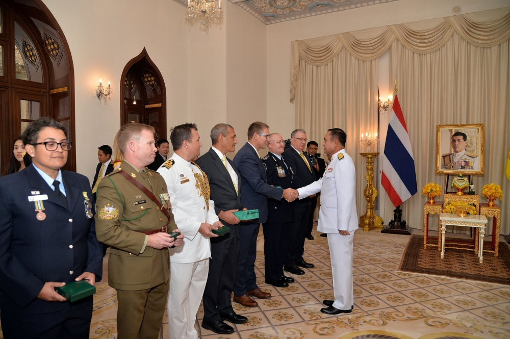 Richard Harris, Australian member of the Thai cave rescue team shakes hands with Thailand's Prime Minister Prayuth Chan-ocha, next to Craig Challen after receiving the Member of the Most Admirable Order of the Direkgunabhorn award at the Government House in Bangkok, Thailand, on Friday. — Reuters
