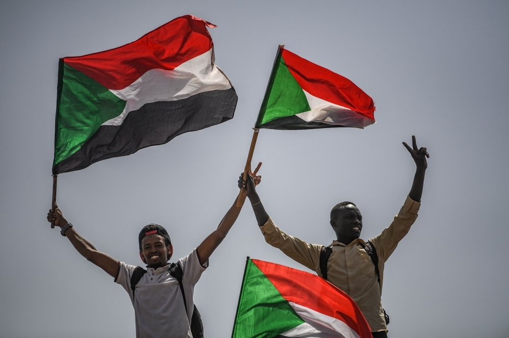 Sudanese protesters flash the victory sign and wave national flags during a rally outside the army headquarters in the capital Khartoum on Friday. — AFP