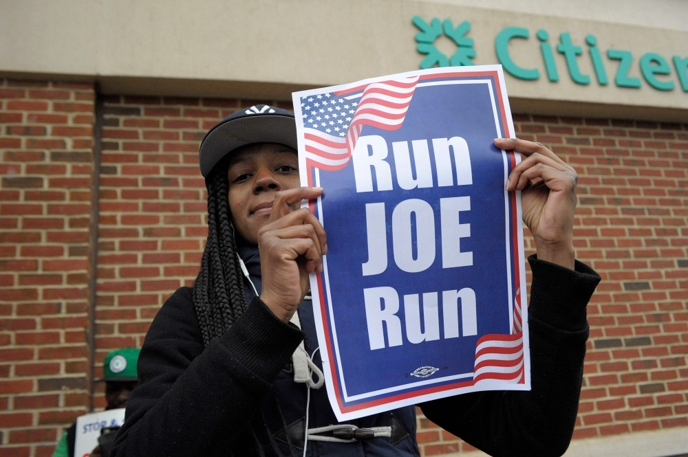 "Jasmin Richardson holds a ""Run Joe Run"" sign after former US Vice President Joe Biden spoke at a rally organized by UFCW Union members to support Stop and Shop employees on strike throughout the region at the Stop and Shop in Dorchester, Massachusetts, on Thursday. — AFP"