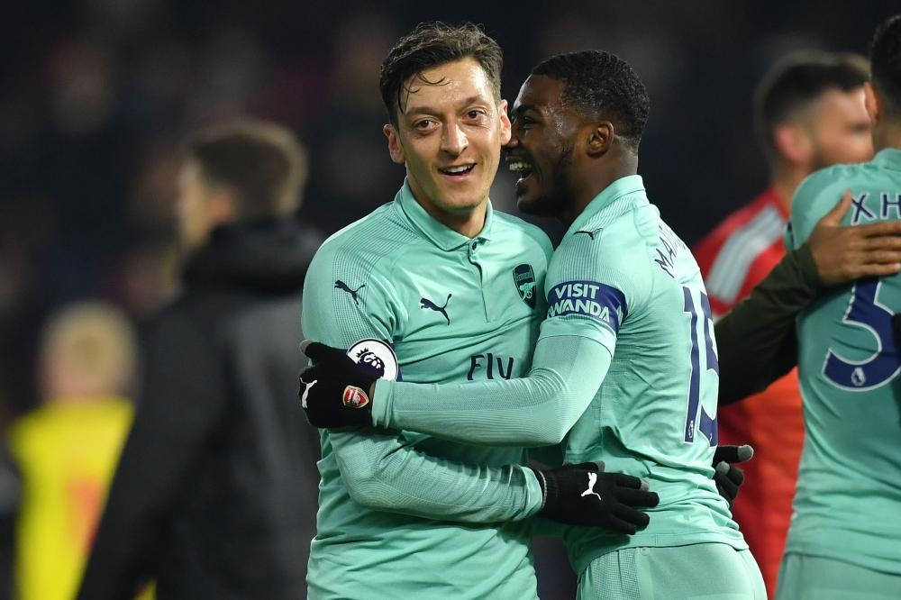 Arsenal's midfielder Mesut Ozil (L) celebrates with teammate Ainsley Maitland-Niles after their English Premier League football match against Watford at Vicarage Road Stadium in Watford Monday. — AFP