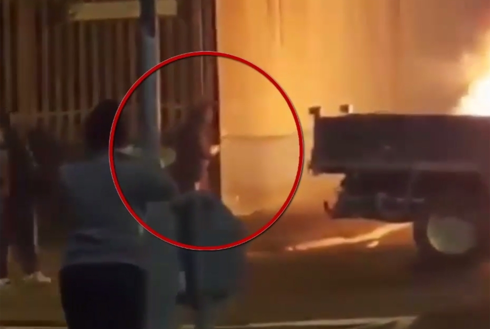 A still image taken from CCTV video footage released by the Police Service of Northern Ireland (PSNI) on Saturday shows a person highlighted in dark clothing with their face covered appearing at the edge of a wall in a scene of the violent disorder during which journalist Lyra Mckee was shot dead in the Creggan area of Derry (Londonderry) in northern Ireland on the night of April 18, 2019. — AFP
