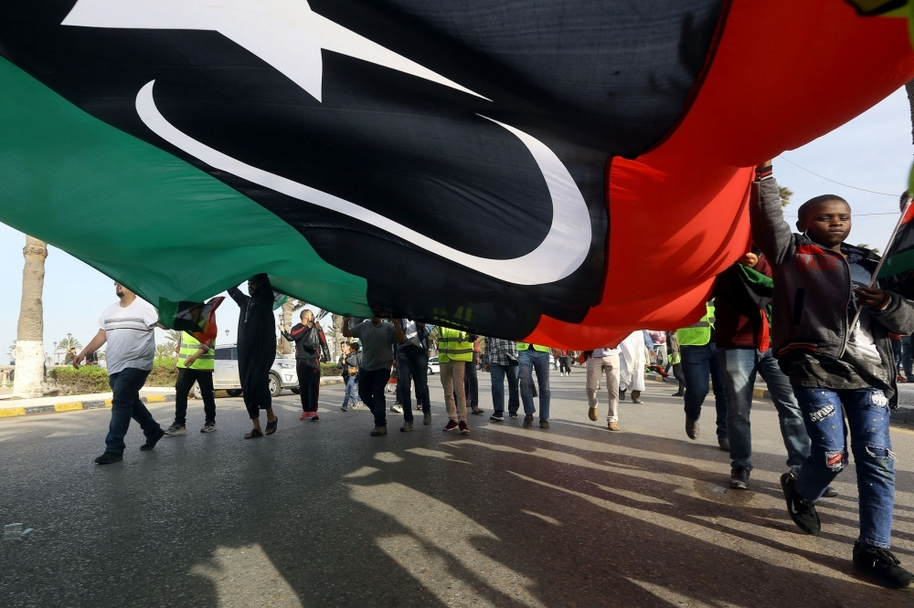 Libyans wave a giant national flag during a demonstration in the capital Tripoli's Martyrs Square. — AFP
