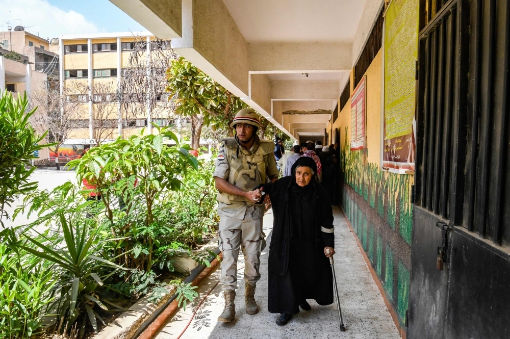 An Egyptian soldier helps an elderly woman to a polling station as she arrives to vote in a referendum on constitutional amendments, at a school in the capital Cairo's northern neighborhood of Shubra, on the first day of a three-day poll, on Saturday.  — AFP