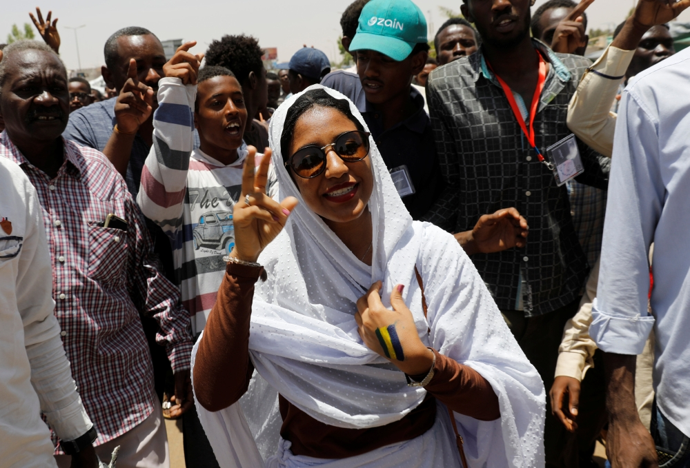 Alaa Salah, a Sudanese protester whose video has gone viral making her an icon for the mass anti-government protests, makes victory sign as she is surrounded by protesters as she tours in front of the Defense Ministry in Khartoum, Saturday. — Reuters