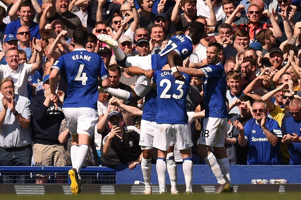 Everton's striker Theo Walcott celebrates with teammates after scoring their fourth goal during their English Premier League match against Manchester United at Goodison Park in Liverpool Sunday. — AFP