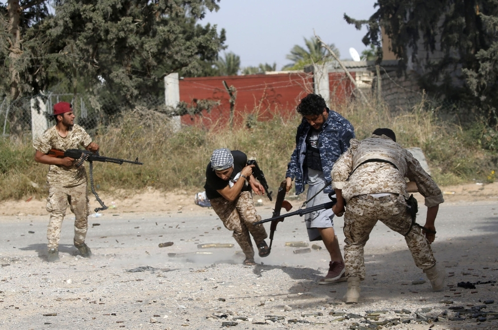 Libyan fighters loyal to the Government of National Accord (GNA) run as they fire their guns during clashes with forces loyal to strongman Khalifa Haftar south of the capital Tripoli's suburb of Ain Zara, Saturday. — AFP